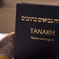 A bilingual Tanakh on a table with a shofar